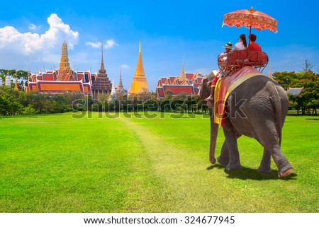 Tourists on an ride elephant dressing with thai kingdom tradition at the Buddhist temple of Wat Phra Kaeo at the Grand Palace in Bangkok,Thailand - stock photo