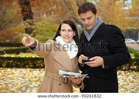 Tourists on city trip using smartphone and city map - stock photo