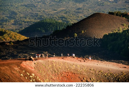 tourists on edge of volcanic Mount Etna - stock photo