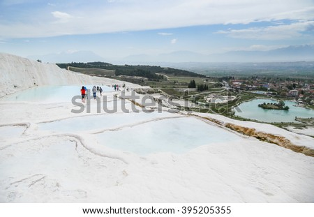 Tourists on Pamukkale Travertine pools and terraces. Pamukkale is famous UNESCO world heritage site in Turkey - stock photo