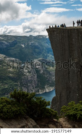 tourists on Preikestolen cliff in Norway, Lysefjord view, Pulpit Rock, tourist attraction towering 604 meters above the sea level, summer 2008 - stock photo