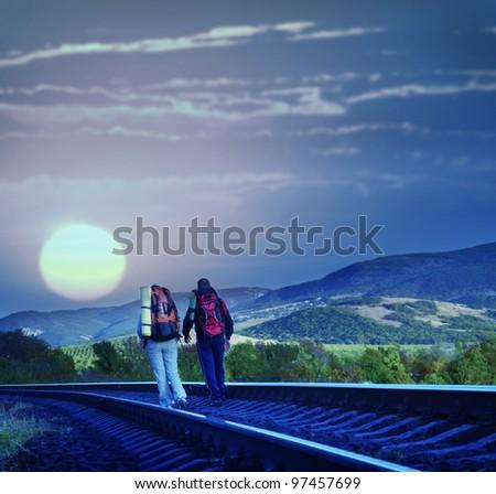 Tourists on railroad tonight - stock photo
