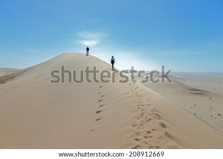Tourists on the slope of the Dune 7 in Sossusvlei plato of Namib Naukluft National Park - Namibia, South Africa - stock photo