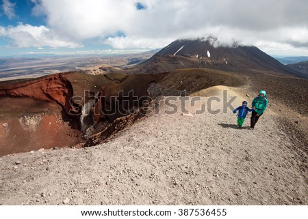 Tourists on the Tongariro Alpine Crossing track walking near Red Crater, New Zealand