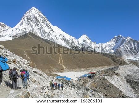 Tourists on the trek at the foot of mount Everest (8848 m) near Gorak Shep village - Nepal, Himalayas - stock photo