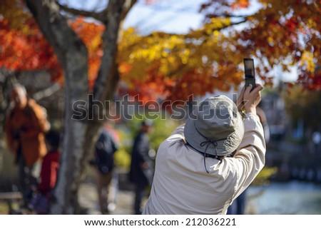 Tourists photograph fall foliage in Kyoto, Japan  - stock photo