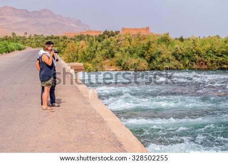 Tourists photographing Draa River, Morocco - stock photo