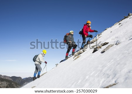 Tourists reaches the top of a snowy mountain in a sunny winter day.