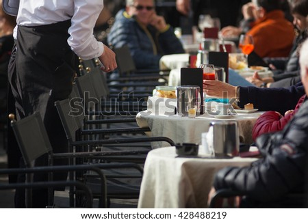 Tourists sitting in the outdoor coffee bar - stock photo