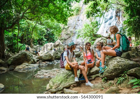 tourists sitting on rocks talking in front of jungle river with waterfall