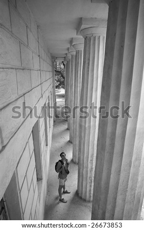 Tourists standing at bottom of colonnade. B&W.