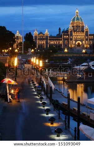 Tourists stroll the causeway of Victoria's Inner Harbor at night buying souvenirs and being entertained by buskers. The Parliament buildings are lit up in the background. British Columbia, Canada.  - stock photo
