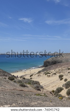 tourists sunbathing and relaxing beautiful Papagayo beach at Lanzarote. Lanzarote a Spanish island, is one of the Canary Islands, in the Atlantic Ocean, appr. 125 km off the coast of Africa. - stock photo