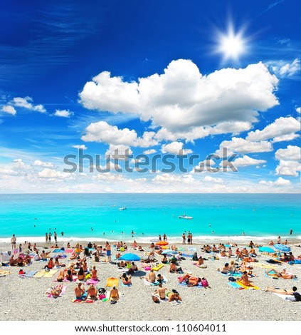 tourists, sunbeds and umbrellas on summer hot day on the beach - stock photo
