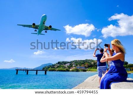 Tourists taking pictures in Corfu. Plane landing at Corfu international airport in Greece. - stock photo