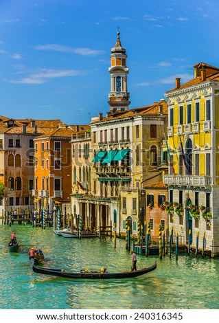Tourists travel on gondolas at canal Venice, Italy . Gondola trip is the most popular tourist activity in Venice. - stock photo