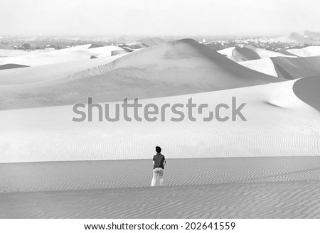 Tourists travel through the dunes in the Atacama Desert - Oasis of Huacachina, Peru, South America (black and white) - stock photo