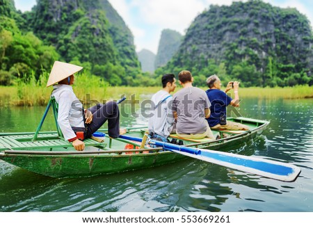 Tourists traveling in small boat along the Ngo Dong River and taking picture of the Tam Coc, Ninh Binh, Vietnam. Rower using her feet to propel oars. Landscape formed by karst towers and rice fields.