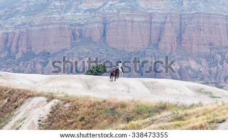 Tourists travelling with horses. Cappadocia in Central Anatolia is a UNESCO World Heritage Site since 1985, Turkey - stock photo