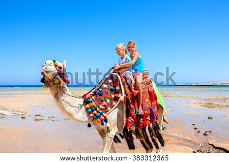Tourists two sisters children riding camel  on beach of  Egypt on blue sky background. - stock photo