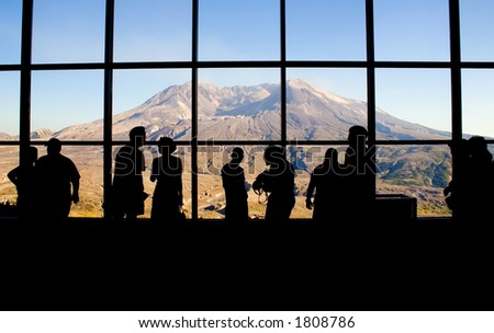 Tourists view Mt. Saint Helens through the windows of the Johnston Ridge Observatory. Washington State, USA. Minor waviness in the sky comes from the glass windows.