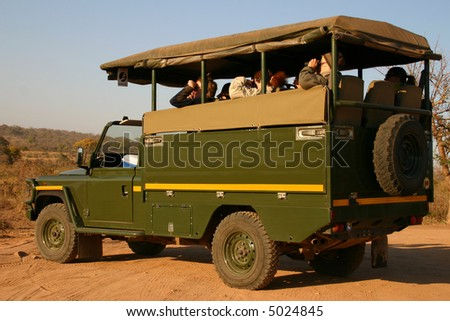 Tourists viewing game from an open safari vehicle.