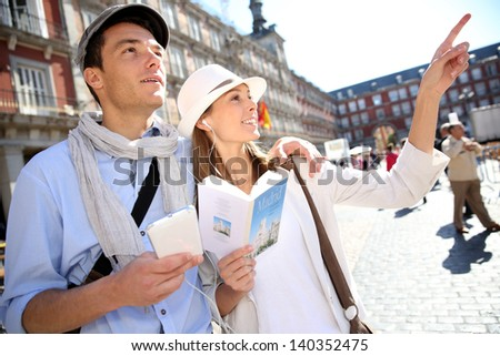 Tourists walking in La Plaza Mayor with traveler guide - stock photo