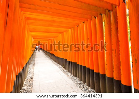 Tourists walking inside the end vanishing point of the repetitive red painted torii gates with black base at the beautiful Fushimi Inari Taisha Shrine in Kyoto, Japan. Horizontal copy space - stock photo