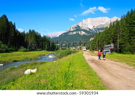 Tourists walking scenic path in Dolomite - stock photo