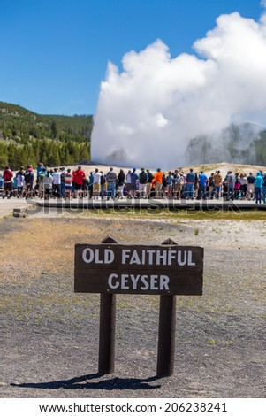Tourists watching the Old Faithful erupting in Yellowstone National Park, USA - stock photo