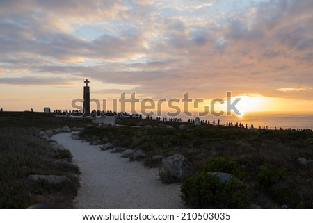 tourists watching the sunset near the cross monument at Cabo da Roca, the western point of Europe - Portugal