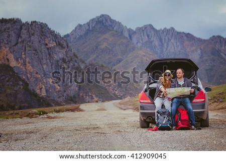 Tourists with a map and backpacks in the car in the mountains - stock photo