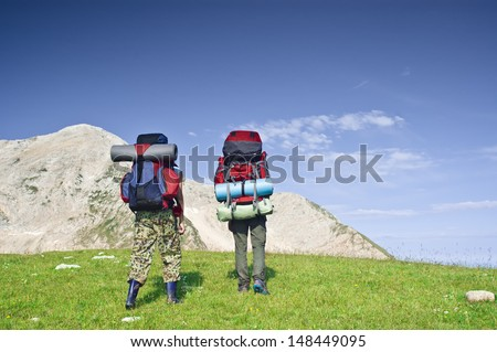 Tourists with backpacks in mountains