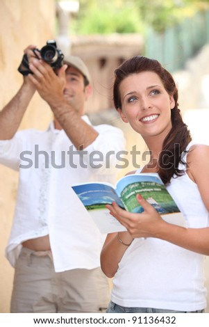 Tourists with camera and travel guide - stock photo