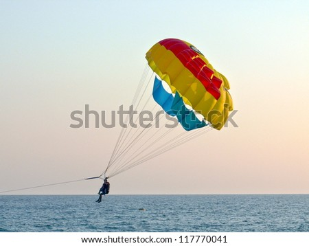 Tourists with parachute above the sea - stock photo
