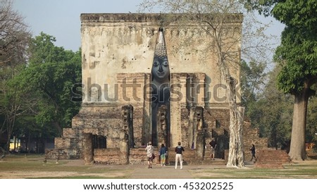 Tourists worshiping an ancient Buddha statue through the gate to Temple Wat Si Chum in Sukhothai Historical Park, Thailand ~ A giant sitting Buddha with the posture of meditation in a Buddhist shrine - stock photo