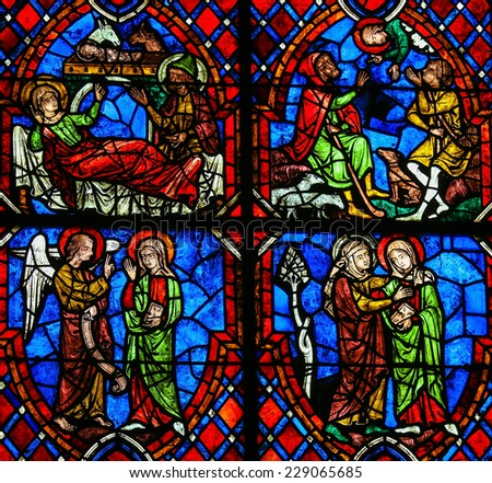 TOURS, FRANCE - AUGUST 14, 2014: Stained glass window depicting various scenes in the Life of Mother Mary, including the Visitation, the Nativity and the Annunciation, in the Cathedral of Tours France - stock photo
