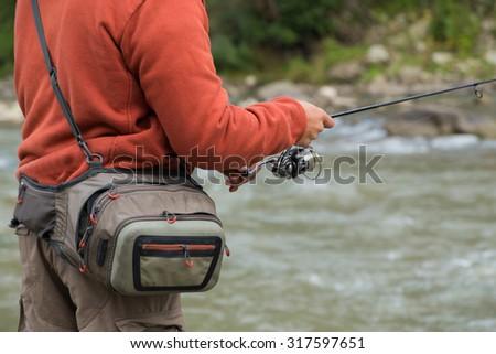 Tout fishing on river - stock photo