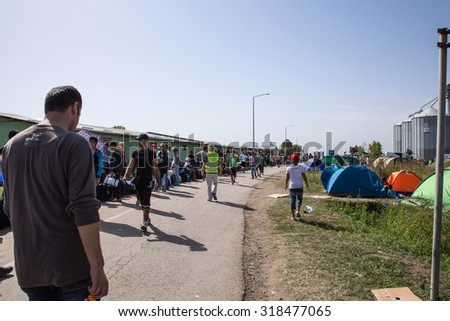 TOVARNIK, CROATIA - SEPTEMBER 19: Stranded Refugees form a waiting line with luggage after their arrival from Serbia on September 19, 2015 in Tovarnik, Croatia. 