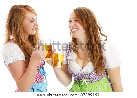 tow bavarian girls with beer skoaling at each other on white background - stock photo