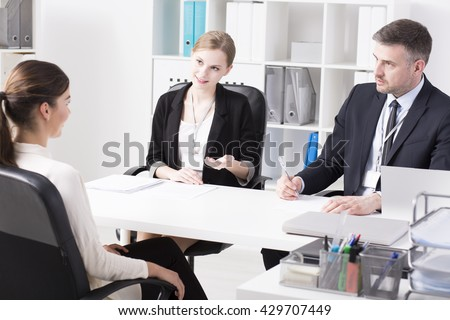 Tow businesspeople and young woman during job interview, sitting in light office - stock photo
