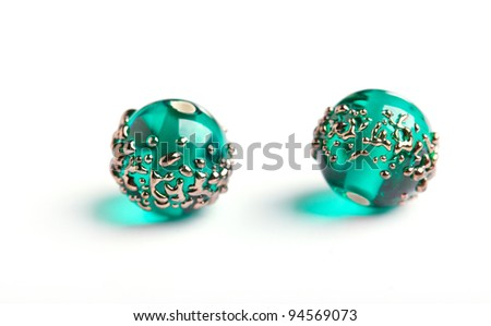 Tow green glass beads with golden pattern closeup on white background - stock photo