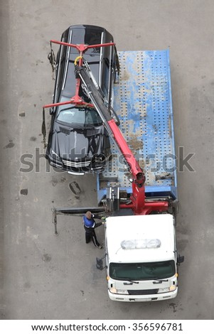 Tow truck is getting crashed black car to the platform on the highway. - stock photo