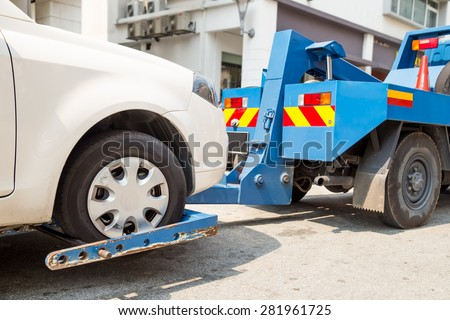Tow truck towing a broken down car with focus on car being towed. - stock photo