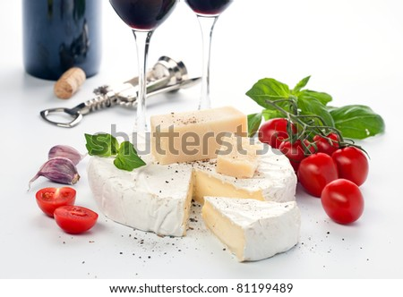 Tow wineglass with red wine and assortment of cheese on white background - stock photo