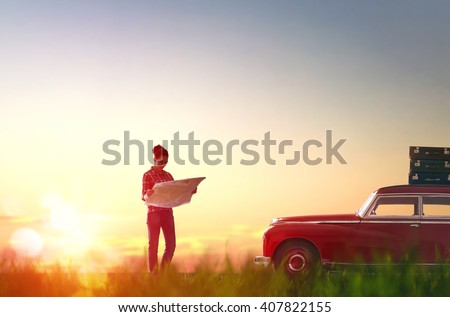 Toward adventure! Beautiful young woman checks the route on a map on the sunset background. - stock photo