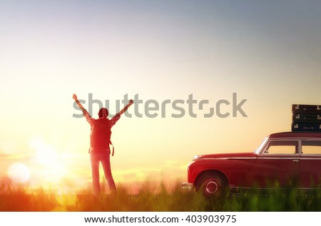 Toward adventure! Girl relaxing and enjoying road trip. Beautiful young woman rejoices dawn. - stock photo