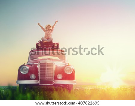 Toward adventure! Girl relaxing and enjoying road trip. Happy child girl sitting on roof of vintage car. - stock photo