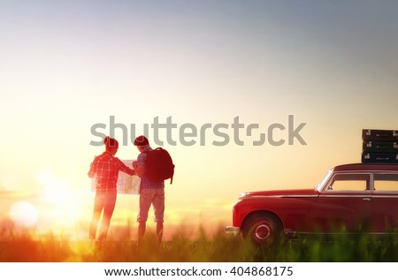 Toward adventure! Man and woman enjoying road trip. Couple searches for a route on the map. - stock photo
