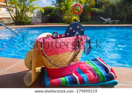 towel and bathing accessories by th side of  blue pool - stock photo